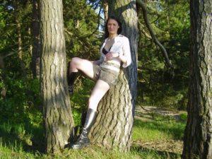 Junges Girl in Lederstiefeln lehnt an Baum