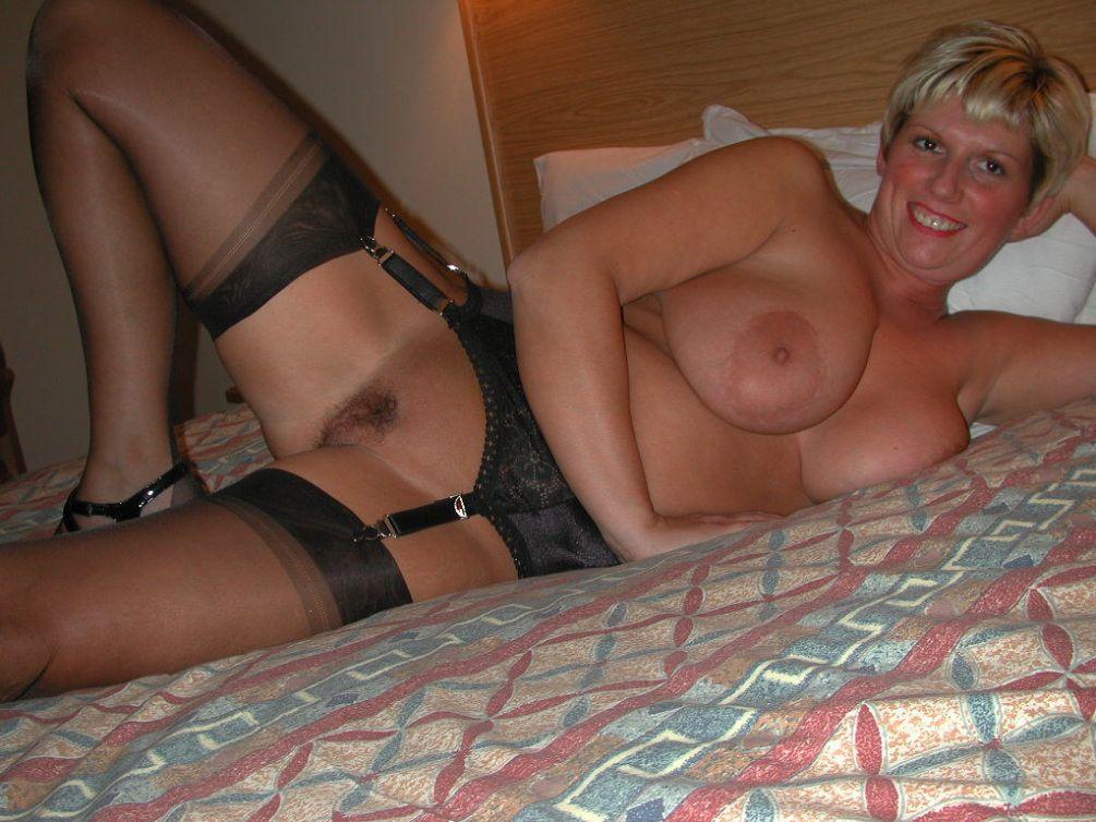 Extrem vollbusige Blondine in sexy Nylons liegt nackt auf dem Bett